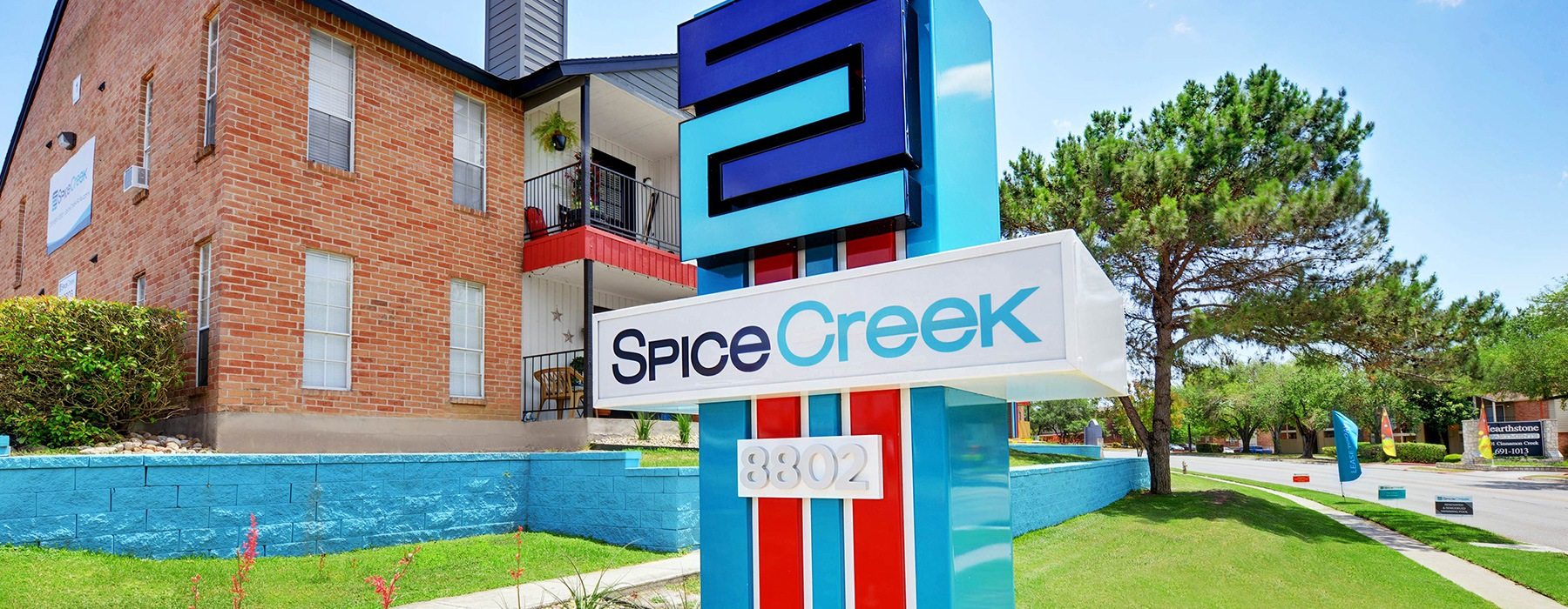 entrance to Spice Creek showing colorful sign and green landscaping
