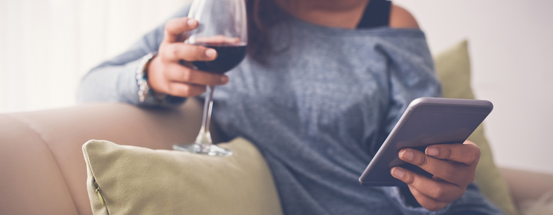 lifestyle image of a woman drinking wine while looking at her mobile device